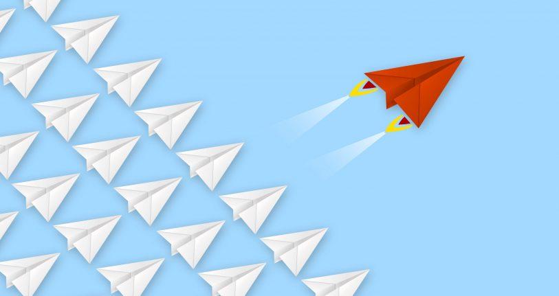 Übersetzer finden: So geht das. Bild zeigt roten Papierflieger vor eine blauen Hintergrund, der einer Schar von gleichförmigen weißen Papierfliegern voraussfliegt.